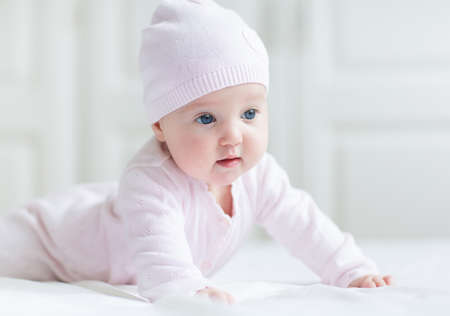 Beautiful baby girl with big blue eyes on a white blanket playing on her tummy wearing a pink knitted hat  photo