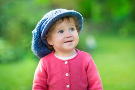 Funny baby girl wearing a big knitted hat playing in a sunny garden on a warm autumn day  photo