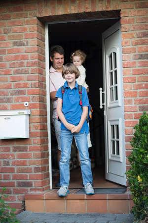 niños saliendo de la escuela: El muchacho lindo de salir de casa para su primer día de regreso a la escuela, el padre y el bebé hermana de pie en la puerta de su casa en el fondo