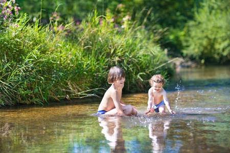 젊은 귀여운 소년과 화창한 여름 날에 아름 다운 강에서 물 속에서 재생 그의 어린 아기 여동생 스톡 콘텐츠