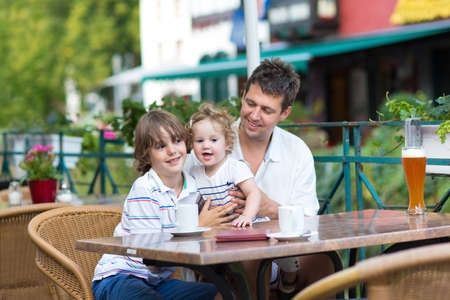 Young father enjoying a meal with his son and baby daughter in an outside cafe on a nice summer day  photo