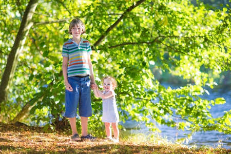 Adorable baby girl holding hands with her brother walking at a river shore on a warm sunny summer day  photo