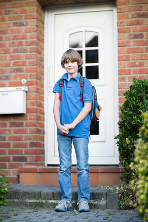 Cute student boy leaving home on his way to the first day at school after summer vacation  photo