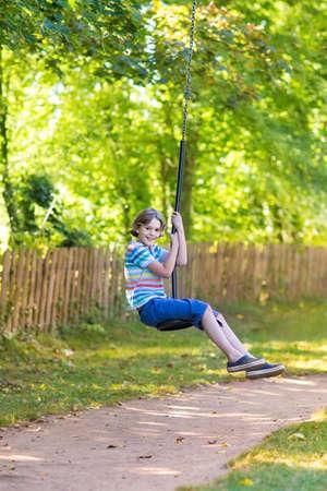 Cute school boy enjoying a swing ride on a playground on a hot sunny summer day  photo