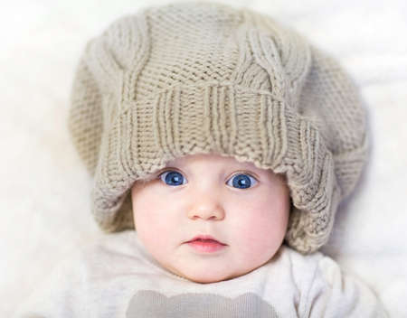 Funny baby in a huge knitted hat wearing a warm sweater relaxing on a white blanket  Stock Photo