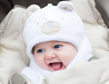 Funny laughing baby in a teddy bear hat sitting in a stroller on c old winter day  photo