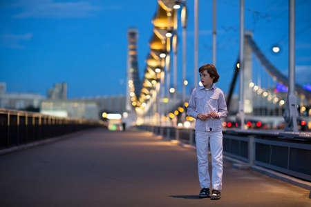 lost city: Little boy walking alone scared on a beautiful bridge in a dark city at night