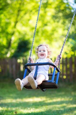 大きな美しい目と巻き毛の日当たりの良い夏の公園の遊び場スイングに乗って楽しく愛らしい赤ちゃん女の子
