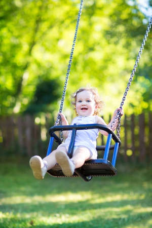 Adorable baby girl with big beautiful eyes and curly hair having fun on a swing ride at a playground in a sunny summer park