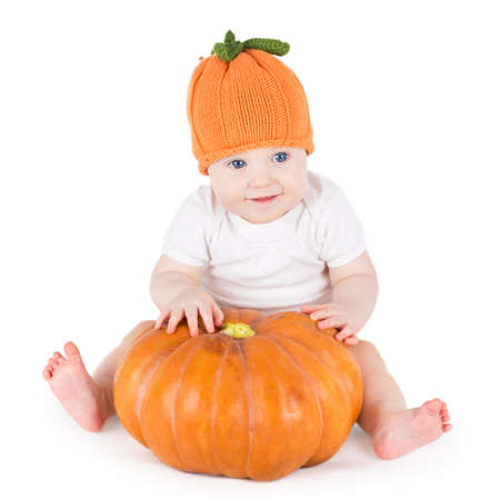 Funny adorable little baby playing with a big pumpkin wearing a knitted pumpkin hat on white background  photo