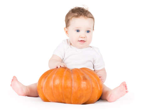 Cute funny baby girl playing with a big pumpkin on white background  photo