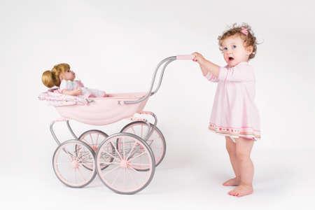 Grappige baby meisje lopen met een pop wandelwagen