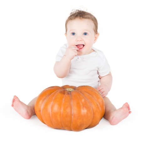 Funny laughing baby girl playing with a huge pumpkin on white background