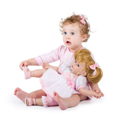 Cute toddler girl playing with her first doll  Stok Fotoğraf