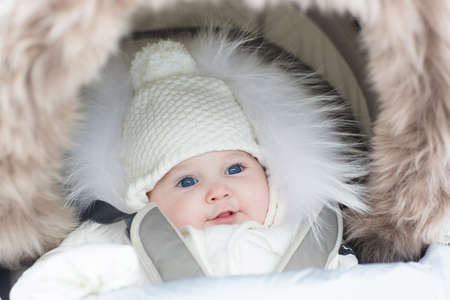 white  hat: Adorable smiling baby girl in a warm stroller wearing a winter snow jacket and a hat on a walk in a cold park  Stock Photo