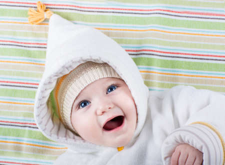 Beautiful little baby with big blue eyes wearing a warm hat and a white winter jacket on a colorful blanket  Stock Photo