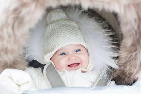 公園で散歩に冬のジャケットと帽子を着て暖かいベビーカーで幸せな笑い赤ちゃん女の子