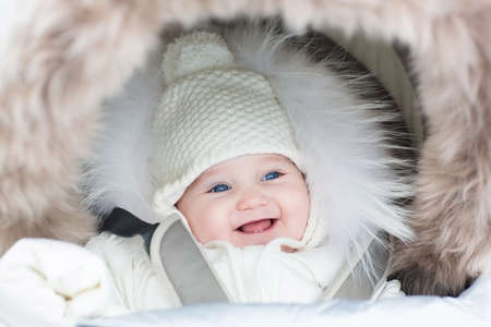 cold season: Happy laughing baby girl in a warm stroller wearing a winter jacket and a hat on a walk in a park