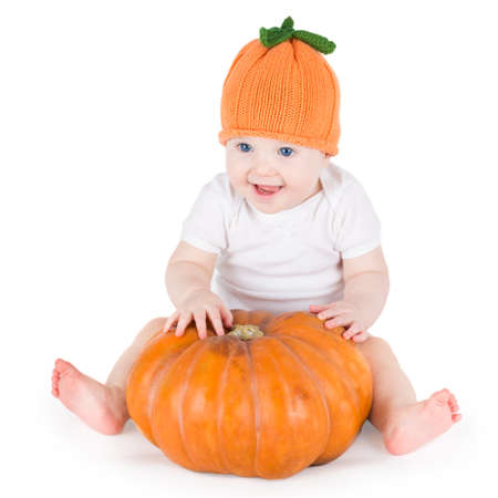 large pumpkin: Sweet laughing baby girl playing with a huge pumpkin wearing a knitted pumpkin hat on white background