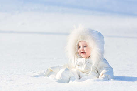warm weather: Adorable laughing baby girl in a warm white snow suit playing in snow on a very sunny and clear winter day in a park