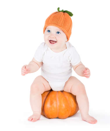 Funny laughing little baby sitting and playing on a huge pumpkin wearing a knitted pumpkin hat on white background  photo