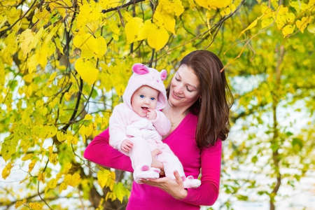 Young attractive mother and her beautiful baby daughter walking in an autumn park under a yellow colorful tree  photo