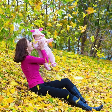 Beautiful young mother and her adorable baby daughter playing on yellow autumn leaves in a park on a sunny fall day  photo