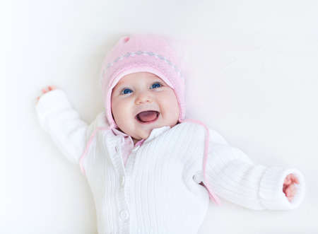 Funny laughing baby girl in a white knitted sweater and a warm pink hat relaxing on a white blanket