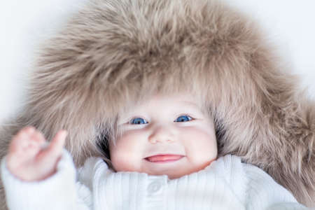 Funny cute baby girl with big blue eyes wearing a huge winter hat and a warm knitted jacket  photo