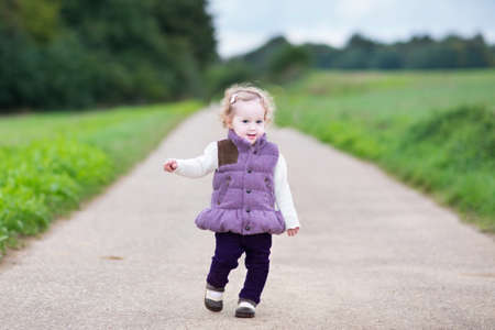 Adorable curly baby girl running on a country road on a cold autumn day  photo