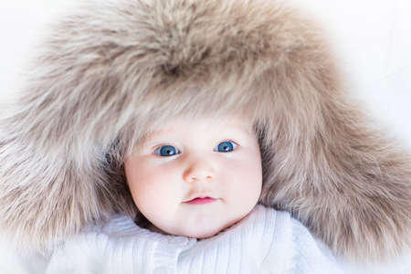 Funny curious baby girl in a huge winter hat  photo