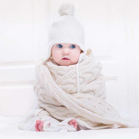 모자와 커다란 니트 스카프를 착용하는 큰 파란 눈을 가진 재미 귀여운 아기 스톡 콘텐츠