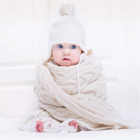 Funny cute baby with big blue eyes wearing a hat and a huge knitted scarf