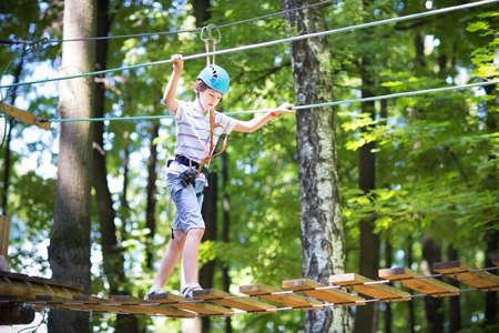 Cute school boy enjoying a sunny day in a climbing adventure activity park
