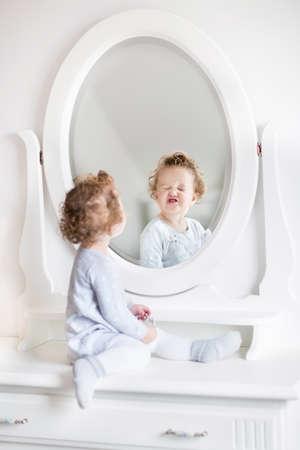 Erg grappig baby meisje met krullend haar op zoek naar haar spiegelbeeld in een prachtige witte kamer met een klassiek dressoir met een ronde spiegel