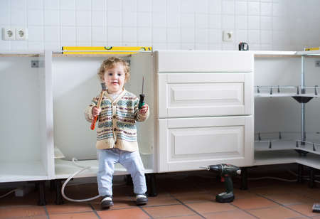 renovating: Little baby helping to assemble a kitchen in a new home