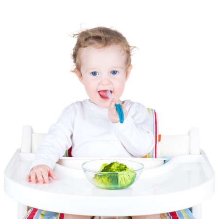 high chair: Cute funny baby with big beautiful blue eyes eating broccoli in a white high chair, isolated on white