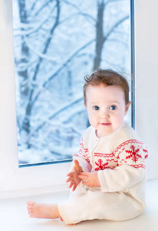 christmas baby: Beautiful baby girl sitting next to a window to a snowy garden on Christmas day
