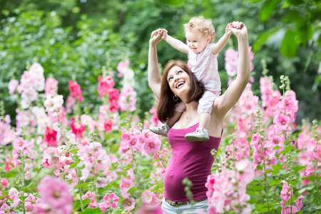 Young active and fit pregnant mother playing with her baby daughter in a blooming garden with pink flowers