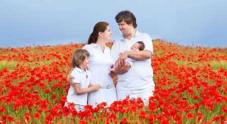 Young beautiful family with a newborn baby daughter and a little son walking in a red flower field  photo