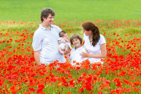 Beautiful young family with a newborn baby daughter and a school age son enjoying a summer day in a red flower field  photo
