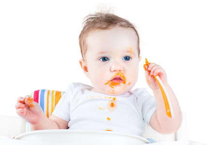 Funny messy baby eating her first solid vegetable food in a white high chair, isolated on white  photo