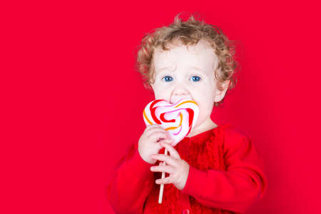 Beautiful curly baby girl eating a heart shaped candy on red background  photo