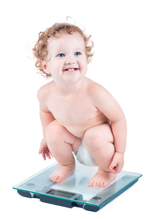 Happy laughing baby watching her weight on a scale, isolated on white  Stock Photo