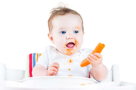 baby eating: Funny laughing baby girl eating a carrot trying her first solid vegetable food sitting in a white high chair, isolated on white