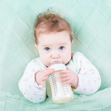formulas: Cute little baby with big blue eyes drinking milk formula out of a plastic bottle relaxing on a green knitted blanket  Stock Photo