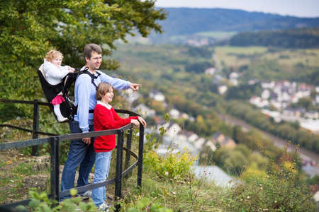Young active father, his son and baby daughter in a back carrier enjoying a beautiful view from an observation deck during a hike in a scenic German mountain landscape  photo