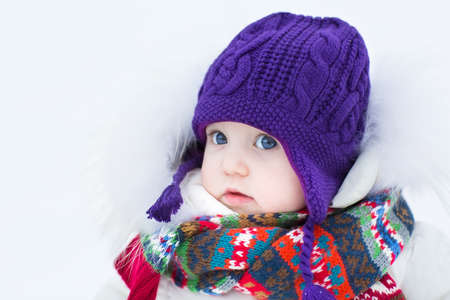 christmas baby: Cute baby girl wearing a warm winter hat and a colorful scarf on a walk in a snowy park