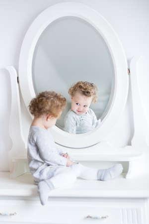 美しいラウンド ミラーと白い寝室の彼女の反射を見て面白いかわいい女の子 写真素材