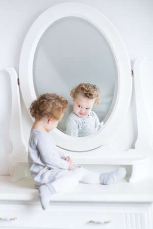 Funny cute baby girl watching her reflection in a white bedroom with a beautiful round mirror  photo